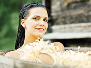 Frau in rustikaler Holzwanne